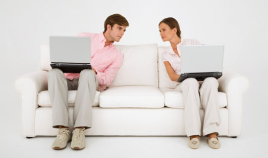 Couple on couch with laptop computers